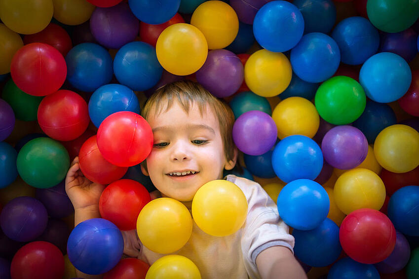 Happy-cute-child-playing-and-having-fun-at-kindergarten-with-colorful-balls