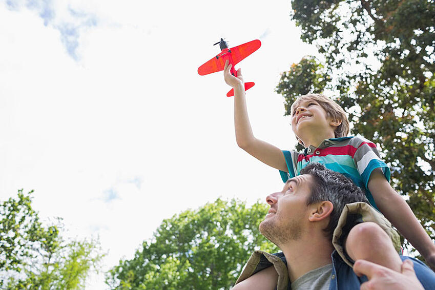 Low-angle-view-of-a-boy-with-toy-aeroplane-sitting-on-fathers-shoulders-at-the-park