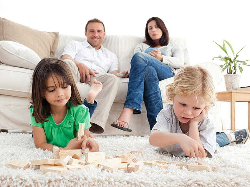 Proud-parents-looking-at-their-children-playing-with-dominoes-on-the-floor-of-the-living-room