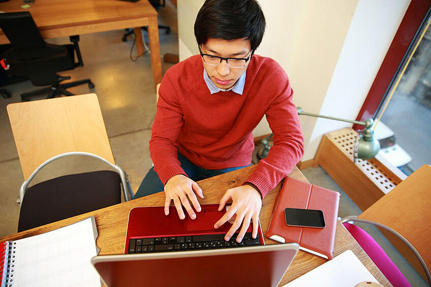 Young-asian-man-in-glasses-working-on-laptop-in-office