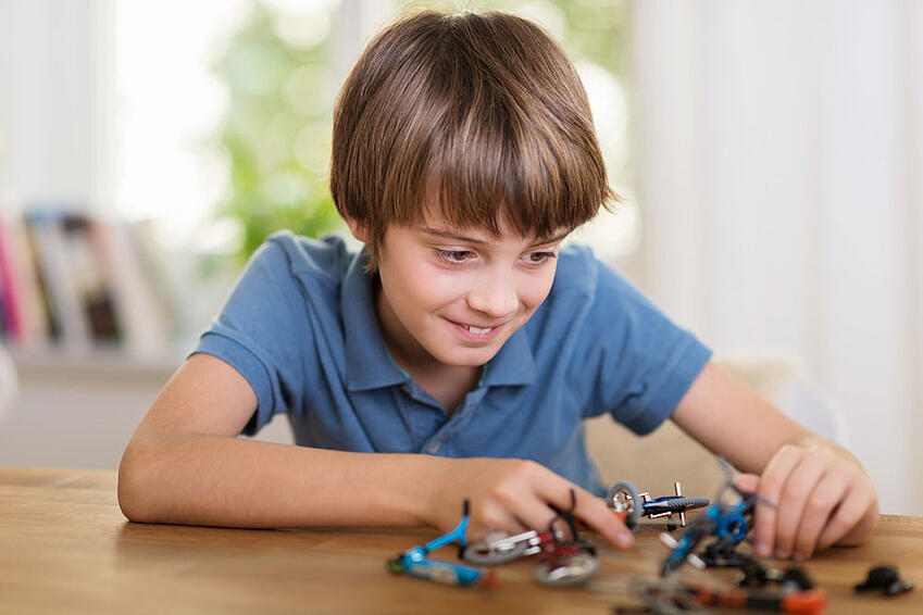 Young-boy-playing-with-a-toy-helicopter-at-home-smiling-a-he-constructs-the-model-in-an-educational-fun-concept